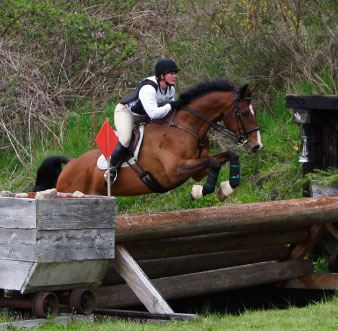 rider going over XC jump with body protector